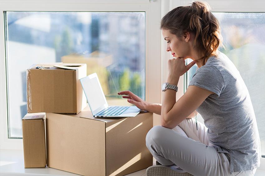 Ultra Umzüge – Eine Frau bedient auf dem Boden sitzend ein Laptop