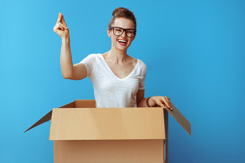 Ultra Umzüge – Eine Frau mit Brille, die bis zum Bauch von einem Karton bedeckt ist