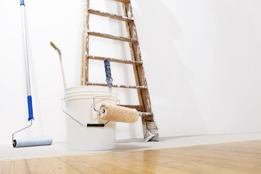 Ultra Umzüge – Leiter, Farbeimer und Farbrolle an einer weißen Wand