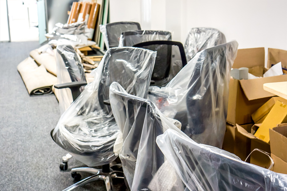 Ultra Umzüge – Eingewickelte Chefstühle und Kartons an einer Wand