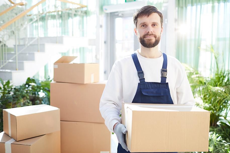Ultra Umzüge – Arbeiter mit blauem Overall hält einen Karton in den Händen
