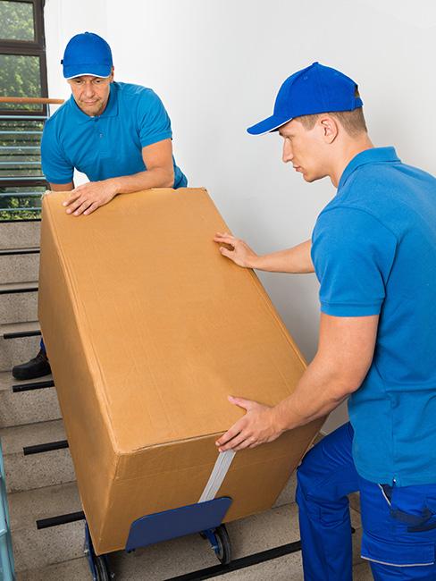 Ultra Umzüge – Umzugshelfer tragen mithilfe eines eines Plattformwagens ein großes Karton die hinunter