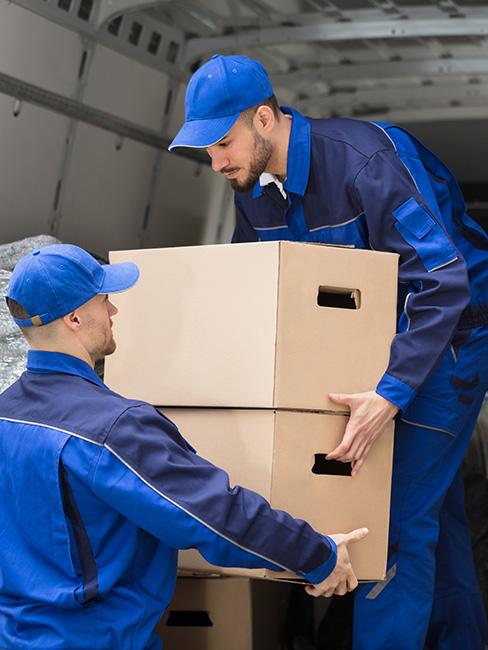 Ultra Umzüge – Möbelpacker beladen einen Transporter mit Kartons