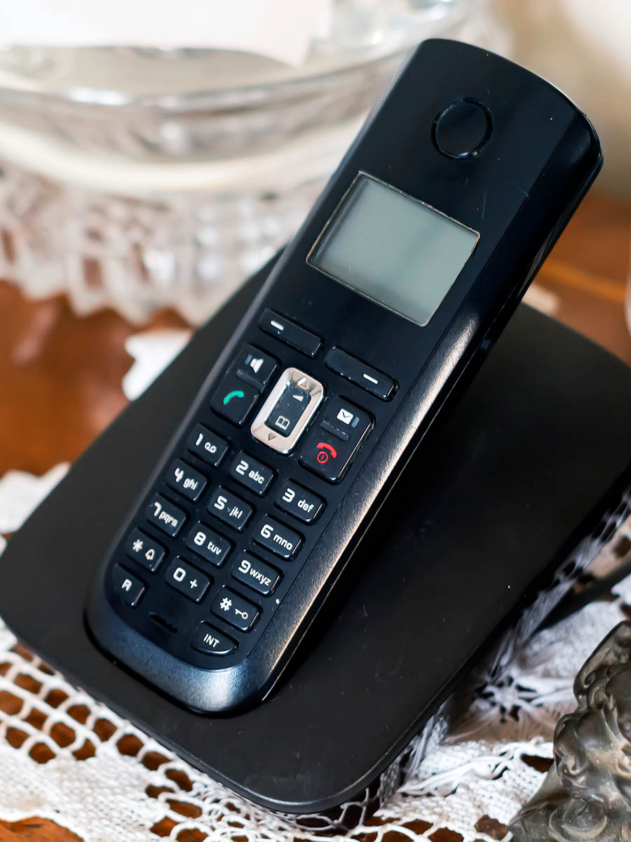 a black plastic cordless phone charging on its cradle inside a classically furnished home with antiques and white crochet. Outdated technology