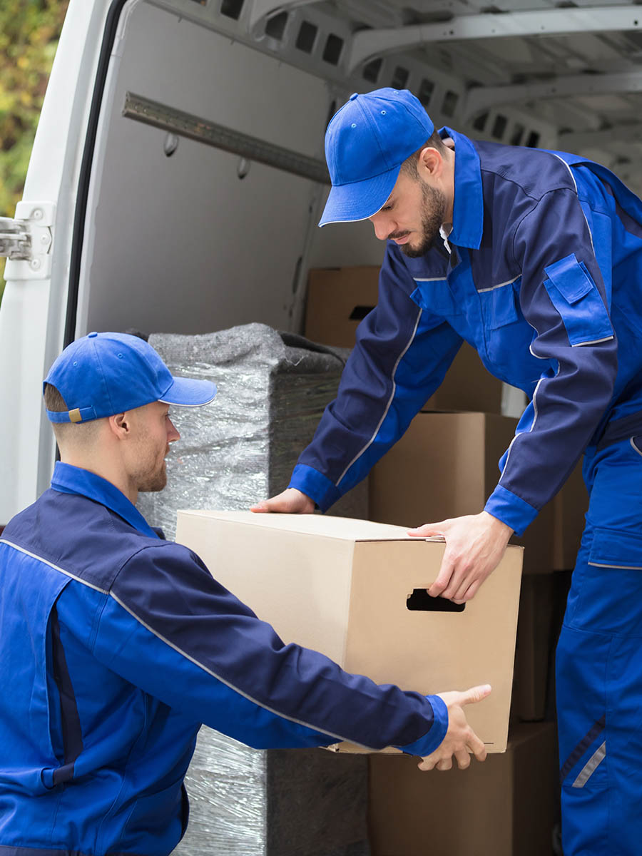 Moving service employee sealing cardboard box with adhesive tape in room, closeup